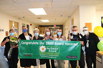 Joey Traywick holding banner with other DAISY awardees
